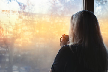 Blonde woman standing by the window, with coffee cup in hands, looking out into the morning light Wall mural