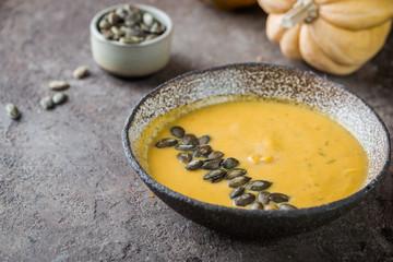 Seasonal autumn food. Healthy Pumpkin soup with cream and organic pumpkin seeds.