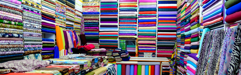 clothes in shop,Rolls of fabric and textiles for sale stacked on shelves in shop, View of cloth rolls of different colors and patterns on shelves in fabric store