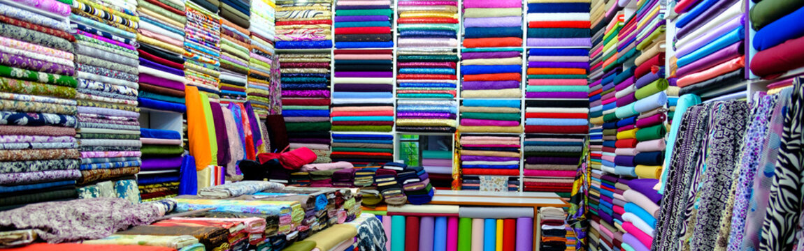 clothes in shop, Rolls of fabric and textiles for sale stacked on shelves in shop, View of cloth rolls of different colors and patterns on shelves in fabric store