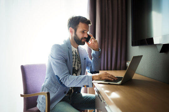 Businessman working on computer in hotel room