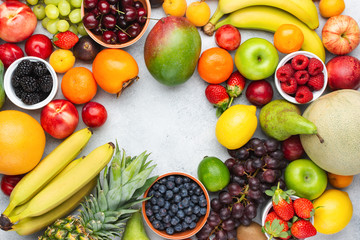 Rainbow fruits background frame, strawberries raspberries oranges plums apples kiwis grapes blueberries mango persimmon on white table, top view, copy space for text, selective focus