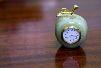retro clock in the shape of an Apple on the polished table