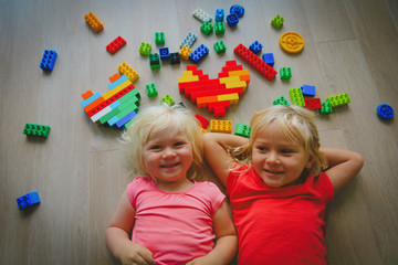 happy cute girls enjoy playing with plastic blocks