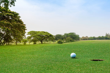 Beautiful landscape of golf course with white golf ball on green grass near hole on background. Golf ball on the green