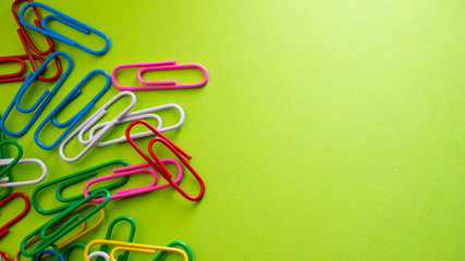 Paper clips on green background with copyspace. View from above with copy space