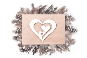 Creative layout with monochrome feathers and heart shaped cut out on envelope. St Valentines Day, love or anniversary concept. Flat lay.
