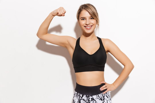 Beautiful young sports blonde woman make fitness exercises isolated posing showing biceps.