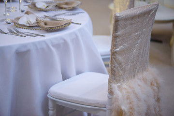 Elegantly covered chair with pearly sequin fabric and beige feathers and restaurant table setting for fine dining with transparent plates, linen napkin, glasses and silverware in order of use