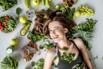 Beauty portrait of a woman surrounded by various healthy food lying on the floor. Healthy eating...