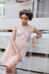 Street fashion. Portrait of an African young woman in pink dress