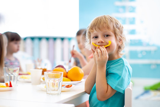 Funny kid boy eating fruits in kindergarten dining room. Child shows smile from paprika slice