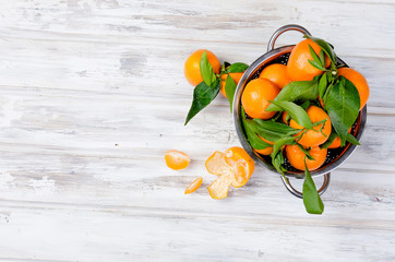 tangerines with leaves on white table