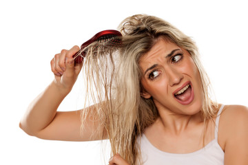 desperate blond woman combing her messy wet hair on white background