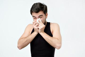 Hispanic young man with black beard being ill sneezing.