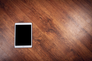 Old white tablet pc on wooden background