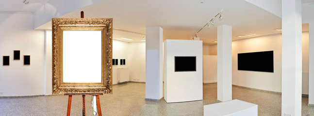 Painter's easel and empty antique golden frame in a exhibition gallery