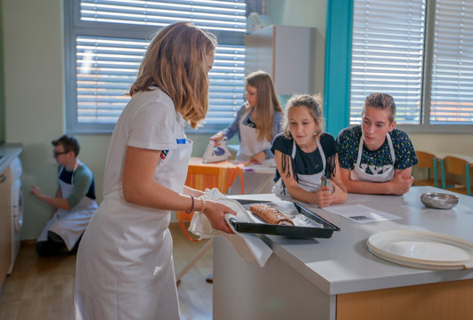 A girl is putting a freshly baked chocolate roll on a table in the classroom. Pupils are having a cooking class.