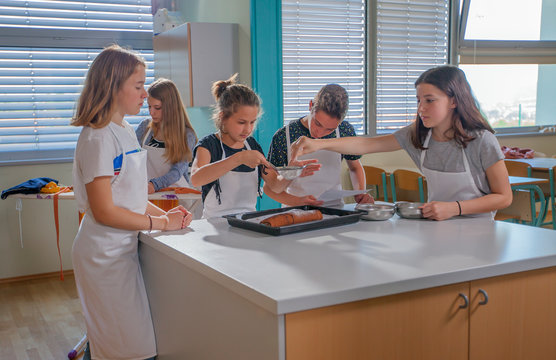 Students have baked a chocolate roll in a cooking class and now, they're sprinkling sugar on it.