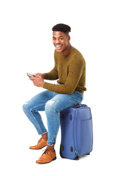 happy travel man sitting with cellphone on suitcase against isolated white background
