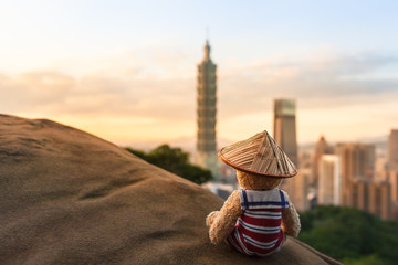 Taipei Travel Adventure / Nostalgic dressed teddy bear wear sailor suit and chinese straw hat, sitting at rock high above modern Taipei city (Taiwan), view to sky and buildings (large copy space)