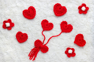 Red crochet wool hearts, flowers and ribbon on white fur background. The concept for 14 February, romantic Valentine day, love affair, love story. Festive overhead photo with place for text.