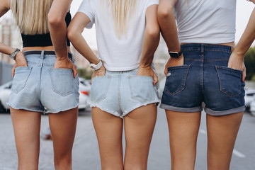 Close up photo of thre shapely girls in jean shorts