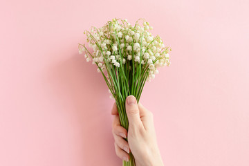 Woman hold in hand bouquet of lilies of the valley