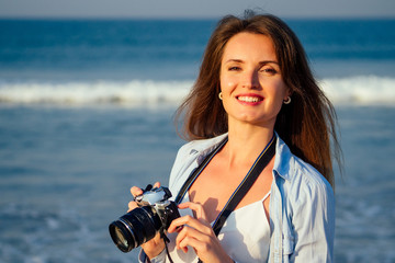 Hipster woman taking photos with retro film camera professional photographer on the beach.Traveling and photography.