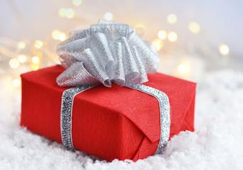 Christmas gift on snow and Christmas lights. Festive Christmas background