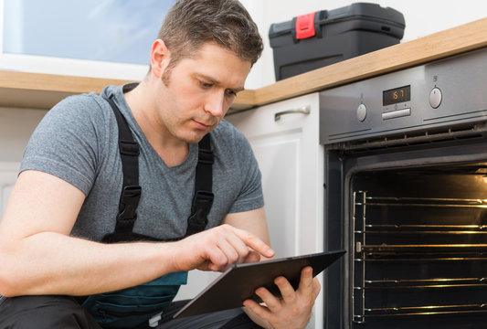 Handyman with tablet pc repairing domestic oven in the kitchen.