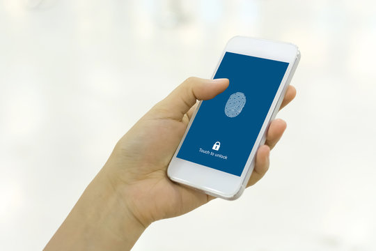 Hand holding smartphone and scan fingerprint biometric identity for unlock her mobile phone