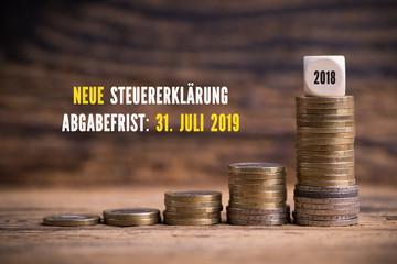 gestapelte Münzen und Erinnerung zur Steuererklärung 2019