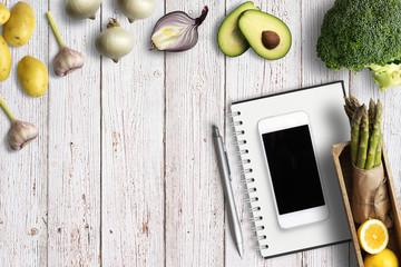 gesunde Lebensmittel und Notizblock mit Smartphone auf Holzuntergrund