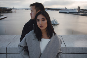 Close up portrait of beautiful asian woman and her husband standing on the rooftop with the scenic view. Oslo, Norway