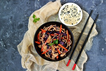 Wheat noodles stir fry with red cabbage, carrots and turkey in a black bowl. Served with black and white sesame seeds. Chinese food. Top view, copy space.