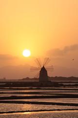 Mulino a vento sulle saline, silhouette al tramonto. Marsala, Sicilia,Italia