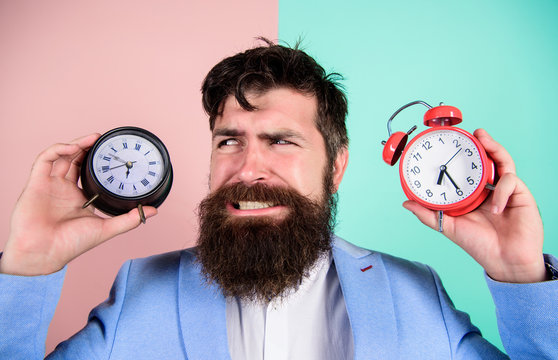 Does changing clock mess with your health. Man bearded hipster hold two different clocks. Guy unshaven puzzled face having problems with changing time. Time zone. Changing time zones affect health