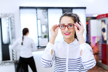 Gorgeous Caucasian woman with curly hair trying out eyeglasses at optician.