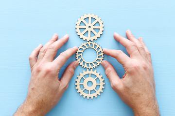 hand placing a cogwheel in set of gears mechanism