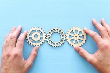hand placing a cogwheel in set of gears mechanism.