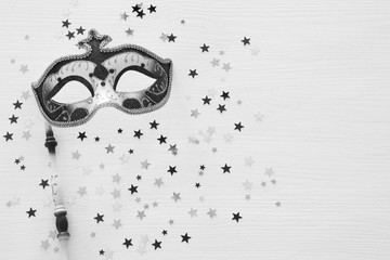 Printed roller blinds Carnaval Black and white image carnival party celebration concept with elegant mask on stick over wooden background and stars. Top view.