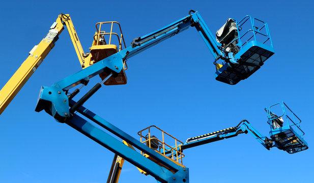 Aerial working platforms of cherry picker against blue sky