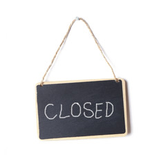 small blackboard sign with the word closed written on it in chalk