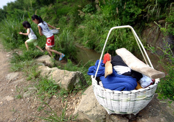 Chinese girls walk home after washing clothes in a brook in the countryside of Jinzhai county.