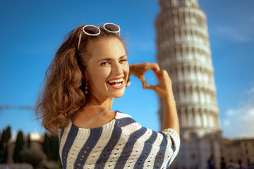 woman against leaning tower showing heart shaped hands