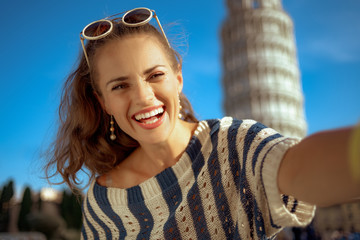 woman in front of leaning tower in Pisa, Italy taking selfie