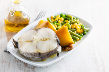 boiled fish with vegetables on white dish
