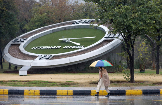 Man holding an umbrella walks in the rain with the backdrop of a giant clock in Islamabad