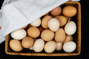 Top view of chicken eggs in a basket on a black background